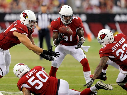 Arizona Cardinals cornerback Antonio Cromartie (31) intercepts a pass between teammates Larry Foote (50), Tony Jefferson (22) and Matt Shaughnessy (91) during the first half of an NFL preseason football game against the Houston Texans, Saturday, Aug. 9, 2014, in Glendale, Ariz. (AP Photo/Rick Scuteri)