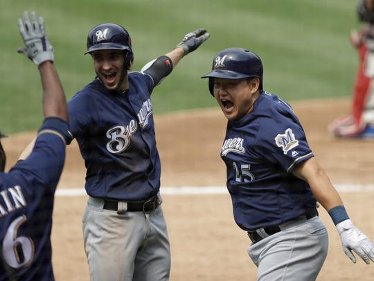 Ji-Man Choi (right) celebrates his grand slam on June 9 against the Phillies with Ryan Braun and Lorenzo Cain.