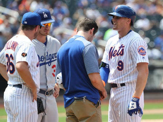 New York Mets manager Mickey Callaway (36) looks on as center fielder Brandon Nimmo (9) is checked by a trainer after being hit by a pitch during the fifth inning against the Los Angeles Dodgers at Citi Field.