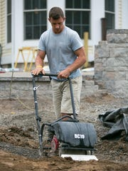Landscaper Jesse Graham works at a home in Pittsford on Tuesday, October 6, 2015.