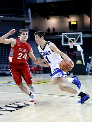 CovCath guard C.J. Fredrick drives to the hoop by Dixie forward Reed Bradfield.