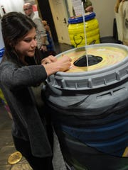 Stephanie Rodriguez cast her ballot for her favorite design of the Rain barrels created by middle schools are being unveiled for public voting at Chase Towers at ArtWalk.