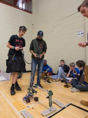 Geoffrey Dressler (left) and Showvik Haque, both seniors at William Penn, compete in the robot arm portion of the High School Division Science Olympiad Competition at Delaware State University.