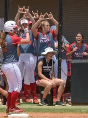 Shellie Landry stands on base as her teammates cheer during Saturday's 9-1 Regional win over Texas.