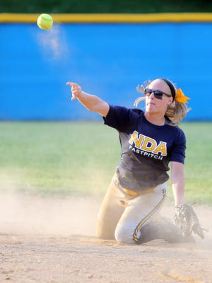 NDA second baseman Cori Ladanyi attempts to throw out a runner from her knees.