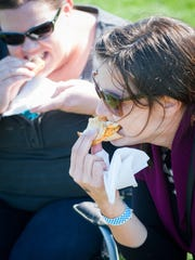 Kasey Herrmann, right, and Lauren Anderson chow down on buffalo chicken and mac'n'cheese grilled cheese sandwiches from the Mad Dash food truck during Yorktoberfest at the York Fairgrounds infield on Saturday, Oct. 25, 2014.