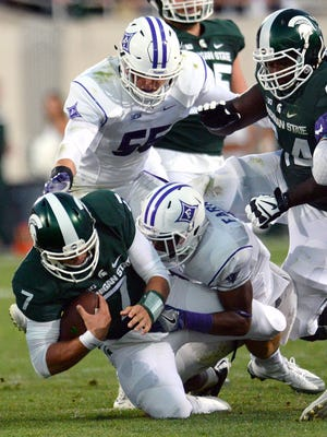 Michigan State University  senior quarterback Tyler O'Connor (7) is tackled after trying to run for a gain in the first half of play against Furman in the Spartan's opening game of the 2016 season Friday, Sept. 2, 2016, in East Lansing.