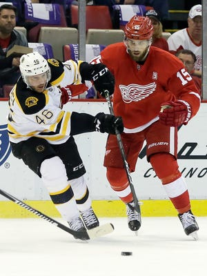 Bruins center David Krejci (46) maintains control of the puck against Red Wings center Riley Sheahan (15) during the first period Saturday at Joe Louis Arena.