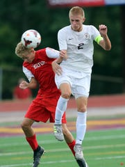 Milford's Joshua Henke and Turpin's Chris Workman battle for the ball.