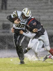 Springfield's Bryan Hayes (32) is tackled by Creek Wood's JJ Higgins. Springfield defeated Creek Wood 42-0.