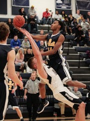 Kameron Gibson of Walnut Hills drives the lane and