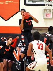 Withrow center Abba Lawal rips down a rebound in the game between the Withrow Tigers and the Anderson Redskins at Anderson High School.