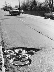 Some clever person decided to make use of the stray hubcaps this hole caused to fall off in 1972
