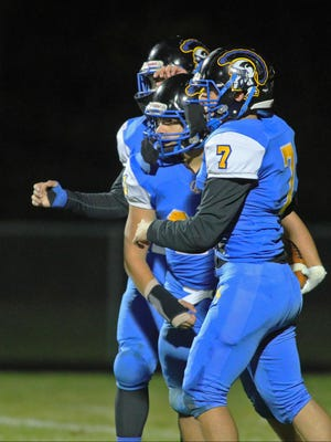 Madison's Isiah Casarez-Ruiz (middle), Angelo Barbour (7) and Robert Gauna celebrate a touchdown during Friday's game against Britton Deerfield.