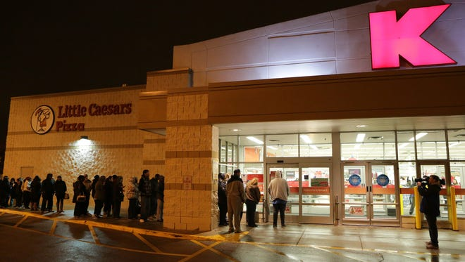 Customers line up outside Kmart on Thanksgiving morning, Nov. 26, 2015,  in Chicago. Kmart stores opened at 6 a.m.