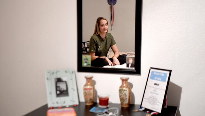 """Mariah, 18, is reflected in a mirror in her bedroom at her foster home with the Wyatt family on Thursday, Dec. 21, 2017. She was put into the foster care system as a young child. """"They're not a family anymore when they're on drugs,"""" she said of her biological family and members of her acquired family struggling with addiction."""