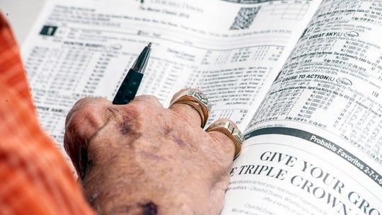 A seasoned gambler eyes a racing form 30 minutes before