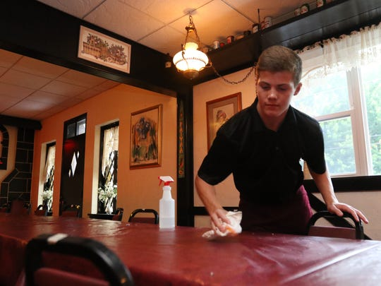 Bryce Shaw, 16, cleans tables in the Buck-A-Neer Supper Club on its last night under current ownership, June 22, 2016.