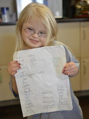 Sophina Lindquist, 6, holds her prayer list for the