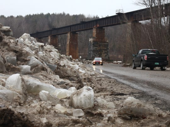 Ice from the Lamoille River is cleared to the side of North Road near the Milton-Georgia town line Thursday afternoon. The river spilled its banks earlier in the day, closing the road to traffic for several hours.