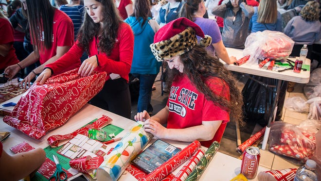 Volunteers wrap presents at Toyota of Muncie during the Secret Families program Saturday morning. Hundreds of volunteers shopped, wrapped and delivered more than 100,000 Christmas gifts for families in need during the event.
