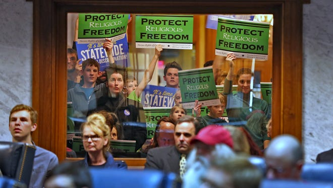 Visitors show signs from outside the packed Senate chambers as SB100 and SB344 were discussed, Wednesday, January 27, 2016.  LGBT legislation was the topic in the Senate Rules Committee hearing with parties from both sides present.