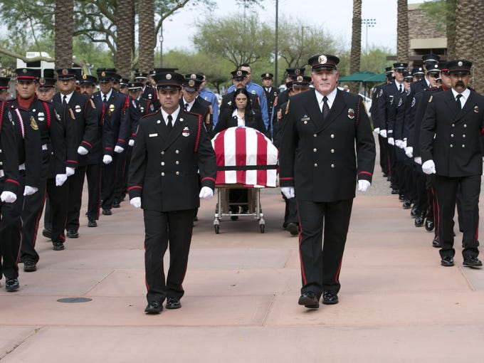 The Phoenix Fire Department honor guard carries the