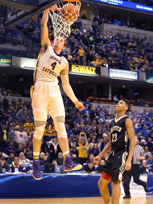 Guerin Catholic High School's Matt Holba, the game's high scorer with 29 points and 14 rebounds, slam dunks over Griffith's Tremell Murphy to put the Golden Eagles ahead 59--53 with 1:06 left in the game and Guerin went on to win 62-56 in the state final to capture the IHSAA Class 3A Boys State Basketball Championship at Bankers Life Fieldhouse in Indianapolis on Saturday, March 28, 2015.