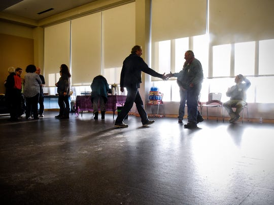 People shake hands and greet each other before the start of a gathering for World Religion Day organized by the Baha'is of Central Minnesota Saturday, Jan. 14, 2017, at the St. Cloud Public Library.