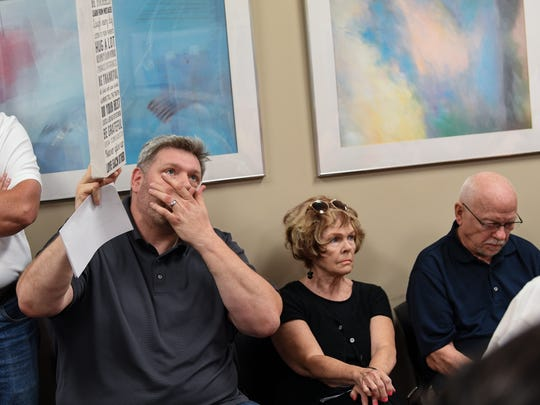 Mike Rawson, left, of 22ft Academy holds up a sign near Ferne Kistner, middle, and Terry Kistner, of Anderson during a Anderson County Land Use and Zoning Board of Appeals meeting at the Anderson County Courthouse Annex in Anderson on Thursday.