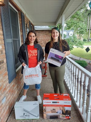 Geneseo band and choir students Megan Plumley, left, and Addie Jorgensen, both sophomores at GHS, show some of the prizes to be awarded in raffle drawings at theannual Harvest Time Music Festival. Prizes include one year of free groceries from Geneseo Fareway. Photo by Claudia Loucks