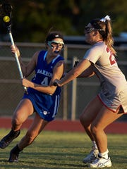 Barron Collier's Emily Browne (4) looks to pass with Vero Beach's Emily McGowan defending Friday, April 21, 2017, during their high school lacrosse game at Vero Beach High School.