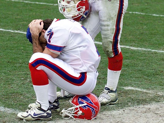Buffalo Bills quarterback Doug Flutie (L) sits dej