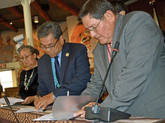 Acting Chief Justice Eleanor Shirley, left, Navajo Nation President Russell Begaye and Speaker LoRenzo Bates sign an agreement that establishes nine priorities for the tribe during the opening of the Navajo Nation Council's summer session in Window Rock, Ariz., last year.