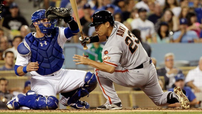 San Francisco Giants' Nori Aoki, right, gets out of the way of a pitch as Los Angeles Dodgers catcher Yasmani Grandal makes the catch during the third inning of a baseball game in Los Angeles.   The Giants declined their 2016 contract options on outfielders Aoki and Marlon Byrd. Both players became free agents Wednesday, Nov. 4, 2015, but the Giants left open the possibility of bringing them back later in the offseason.