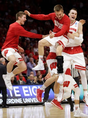 Wisconsin forward Sam Dekker, right, celebrates with teammates after beating Arizona 85-78 in a college basketball regional final in the NCAA Tournament on Saturday in Los Angeles. Wisconsin will play in the Final Four in Indianapolis.
