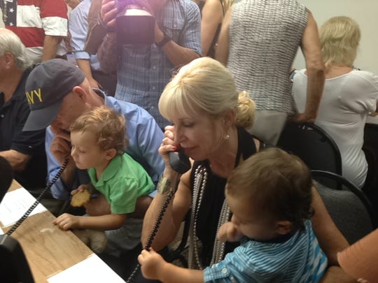 Gov. Rick Scott and his wife call voters at the Naples campaign office with the help of their grandsons, Auguste and Quinton Guimard.