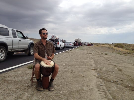 Chris Friedel of Nevada City, Calif., plays the drums along the side of the road just south of the Burning Man entrance on Monday, Aug. 25.