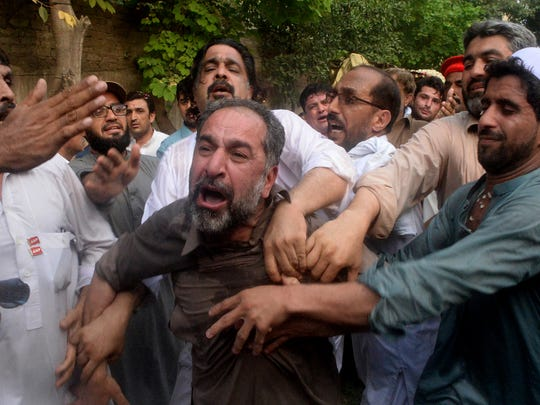 People try to comfort a supporter of Pakistani politician Haroon Ahmed Bilour, a victim of a suicide bombing at an election rally, during his funeral in Peshawar, Pakistan on July 11, 2018. The Pakistani Taliban claimed responsibility for an overnight suicide bombing two weeks before nationwide elections.