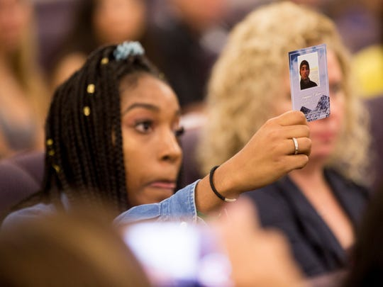 Tyra Hemans, 19, a senior at Marjory Stoneman Douglas, holds up a photo of her friend Joaquin Oliver, one of the victims of the mass shooting that took place at the school last week, during an initial meeting with Florida State Senators, including Senate President Joe Negron, at The Capitol Complex early Wednesday, Feb. 21, 2018 in Tallahassee, Fla.