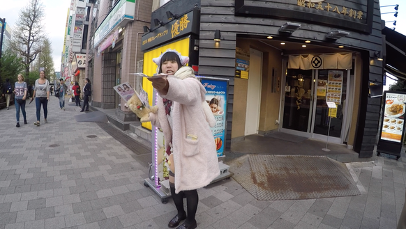 A woman hands out a flyer for a local maid cafe in