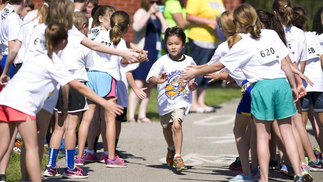 "Photos by DENNY SIMMONS / COURIER & PRESS Ashton Giles, 7, nears the finish line at the ""Wildcat Mile"" race in Downtown Newburgh on Monday morning."