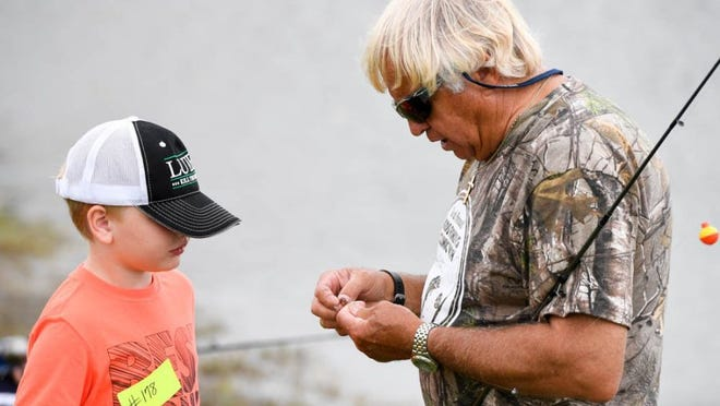 MIKE LAWRENCE / COURIER & PRESS Professional angler and TV host Jimmy Houston gives Luke Gerhardt some professional advice on putting a worm on a hook during the third annual Kids Fishing Clinic held at Expressway Chevrolet in Mount Vernon last Saturday.