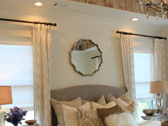 Designer Julie McCoy hung a mirror above this upholstered headboard. The look is simple but elegant.