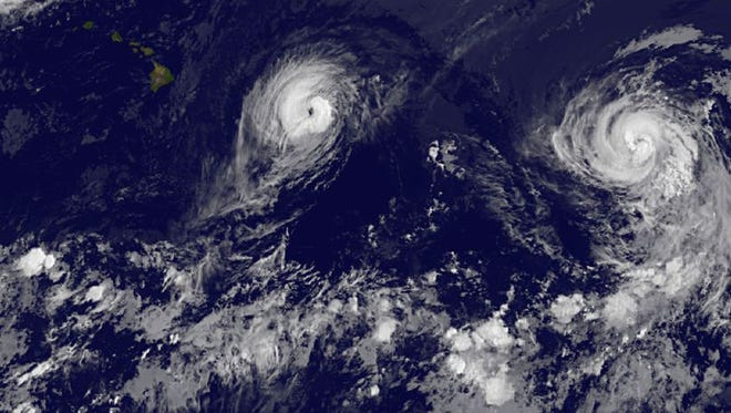 This image provided by NOAA taken Thursday Aug. 7, 2014, at 2 a.m. ET shows Hurricane Iselle, left and Hurricane Julio.