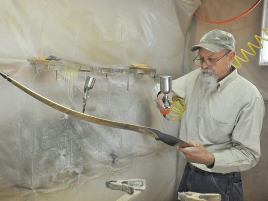 """Mike Treadway applies a finishing coat to one of his handmade works. """"That's where I strive on my bows, to have a nice finish on it,"""" he said ."""