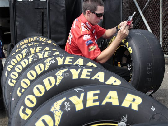Greg Biffle crew member Todd Chafee checks race tires in the garage area Friday at Watkins Glen International during practice for Sunday's Cheez-It 355 at The Glen.