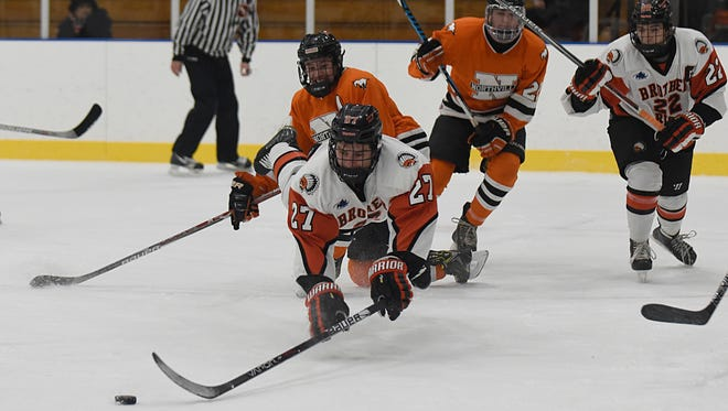 Brother Rice's Blake Tosto (27) dives for a loose puck during Thursday's victory over Northville.