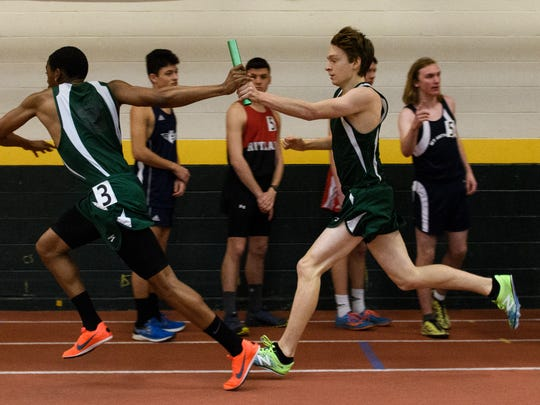 The St. Johnsbury's Nathaniel Atkins hands off the baton to Mackay Breton during the 4x800m relay during the high school indoor track and field championships at Gutterson Field House on Saturday February 10, 2018 in Burlington. (BRIAN JENKINS/for the FREE PRESS)