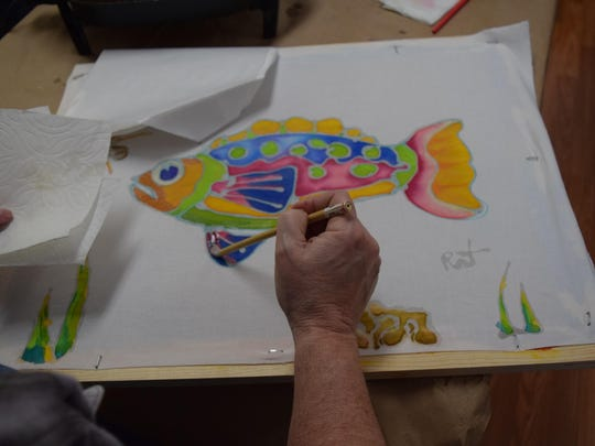 Color is added to a batik fish.